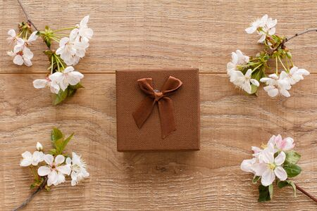 Gift box with branches of flowering cherry and apple trees on the wooden background. Top view. Concept of giving a gift on holidays.