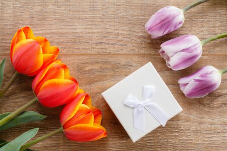 White gift box with red and lilac tulips on wooden boards. Greeting card concept. Top view.
