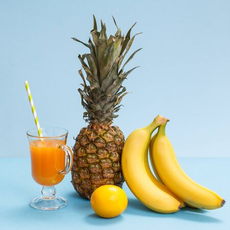 Glass of fruit juice, fresh pineapple, lemon and bananas on blue background.