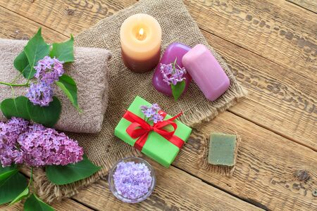 Terry towel, soap and sea salt for bathroom procedures, burning candle, gift box and lilac flowers on sackcloth and old wooden boards. Top view. Spa products and accessories.