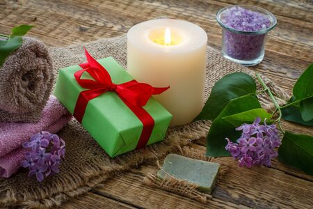 Terry towels for bathroom procedures, gift box, sea salt, burning candle and lilac flowers on sackcloth and old wooden boards. Spa products and accessories. Reklamní fotografie