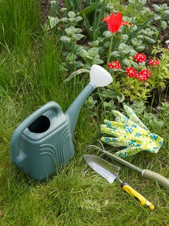 Watering can, rake, shovel and gloves next to a flowerbed with green grass on the background. Top view. Garden tools.