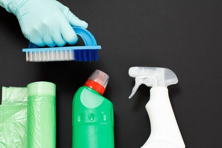 Woman's hand in a protective glove with a brush and a washing and cleaning set on the black background. Top view.