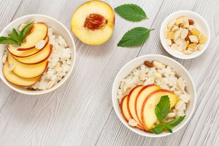 Sorghum porridge with pieces of peach, cashew nuts and almond in porcelain bowls, a fresh peach on wooden boards. Vegan gluten-free sorghum salad with fruits. Top view.