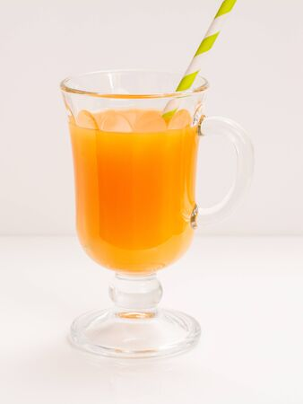 Glass of fruit juice with a straw on white background.