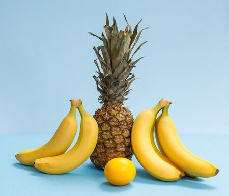 Natural composition with tropical fruits. Fresh pineapple, bananas and a lemon on the blue background.