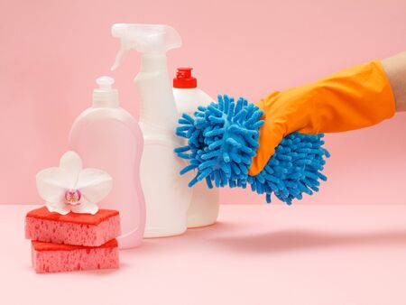 Plastic bottles of washing liquid, sponges and a hand in a rubber glove holding a doormat on the pink background. Washing and cleaning set. Imagens