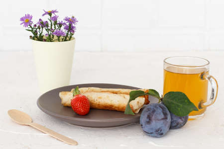 Homemade pancakes filled with cottage cheese, a strawberry on a plate with a wooden spoon, a cup of tea, plums and flowers.
