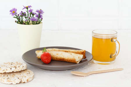 Homemade pancakes filled with cottage cheese, a strawberry on a plate with a wooden spoon, a cup of tea, puffed rice cakes and flowers.