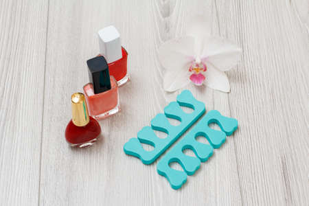 Bottles of nail polishes and toe separators on gray wooden background. A set of cosmetic tools for professional hardware manicure. Top view.