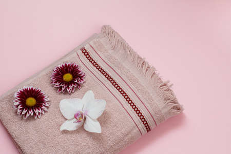 Soft terry towel with a white orchid and red flower buds on the pink background. Top view.