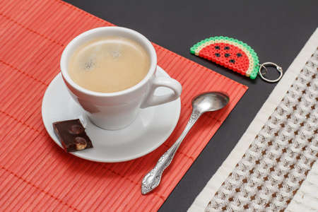 Cup of coffee on saucer with a piece of chocolate bar, a spoon, a bamboo napkin, a trinket and a kitchen towel on the black background. Top view.