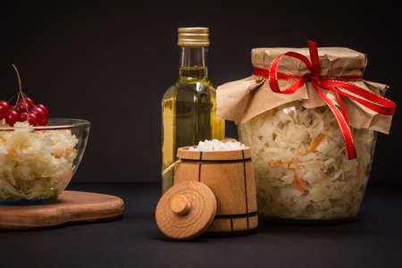 Homemade fermented cabbage in a glass bowl and a jar, a small wooden barrel with salt and a bottle of oil in the black background. Vegan salad. Dish is rich in vitamin U. Food great for good health. Reklamní fotografie