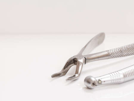 Set of metal dental instruments for dental treatment on the white background. Medical tools. Close-up view. Shallow depth of field. Focus on a stainless steel dental tongs. Zdjęcie Seryjne