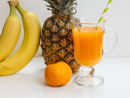 Glass of fruit juice with a straw, a fresh pineapple, bananas and a mandarin on the white background.