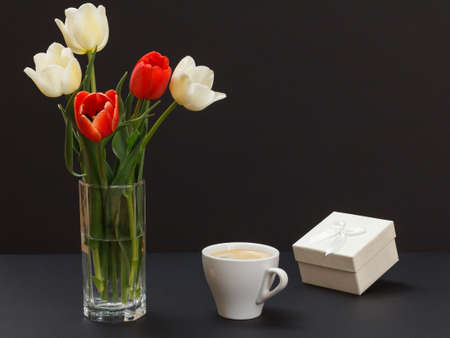Bouquet of yellow and red tulips in glass vase, a gift box and a cup of coffee on a black background.