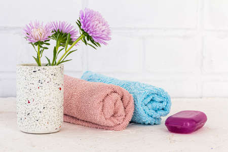 Towels, soap and flowers of asters on a white background. Woman cosmetics and wash accessories.