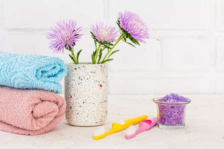Can with sea salt, towels, toothbrushes and flowers of asters on a white background. Woman cosmetics and wash accessories.