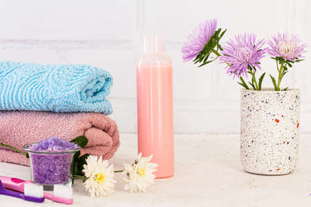 Can with sea salt, toothbrushes, a bottle of shampoo, towels and flowers of asters on a white background. Woman cosmetics and wash accessories.