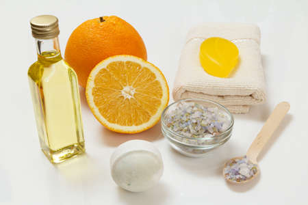 Cut orange with a whole one, a terry towel, a bottle with aromatherapy oil, soap, a bath bomb and a wooden spoon with sea salt on the white background. Spa products and accessories.