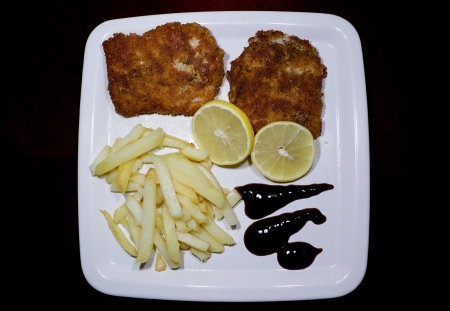 Fish, chips, lemon and dressing in a white plate