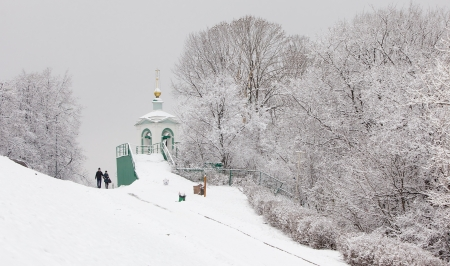 A couple walk past snowfall trees in Moscow photo