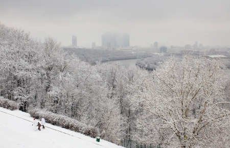 A family walk past snowfall trees in Moscow