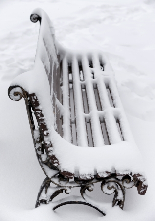 A bench with snow in a park