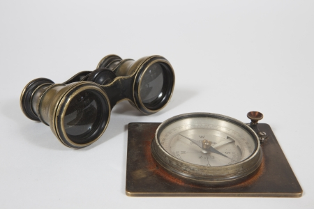 An old binocular and compass on white background Stock Photo