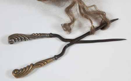 An antique curling iron with hair photo