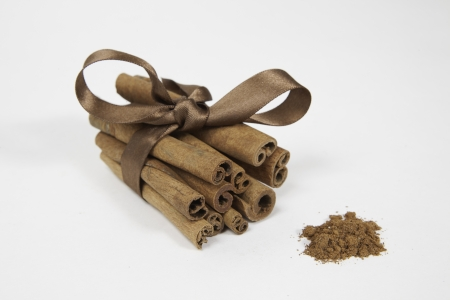 Sticks and powder of cinnamon on white background