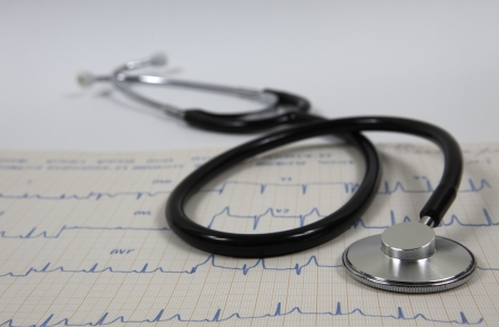 Stethoscope with cardiogram on white background