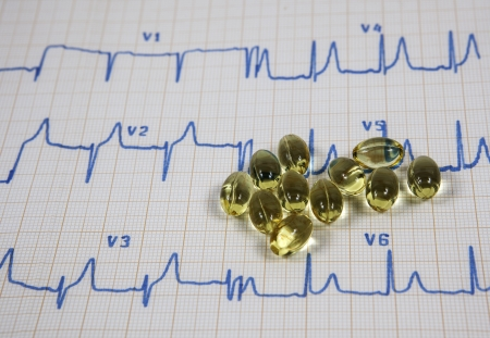 Cardiogram with vitamins on white background Stock Photo