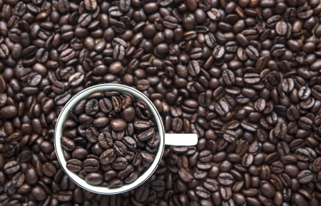 A cup of coffee beans with beans background
