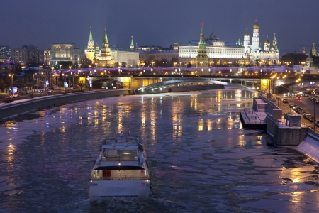 Frozen river with kremlin background and boat