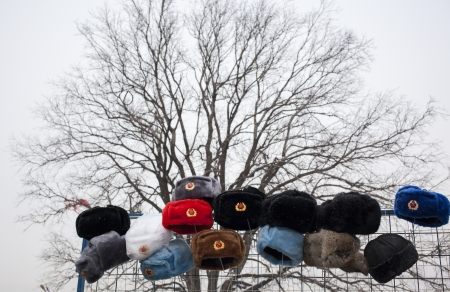 stalker: Russian military style fur hats displayed on a metal net at a street market