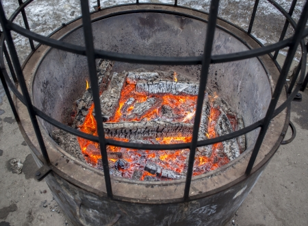 stoking: An outside fireplace near ice rink in a park
