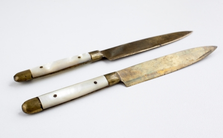 Two vintage brass knifes with pearl handle Stock Photo
