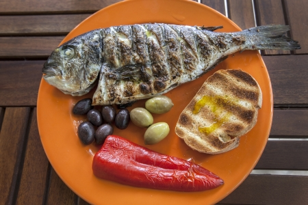A fresh cocked fish with roasted bread, olives kalamata and pepper Stock Photo
