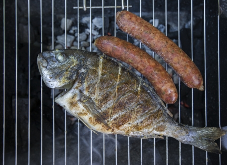A barbecue with a fresh fishes with sausages