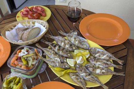 Barbecue fresh fishes with lemon, bread, tomatoes, wine and marinated vegetable