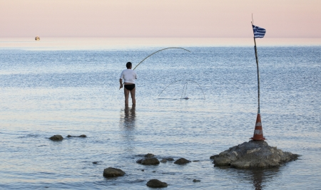 A man is fishing during sunset in a beach in the Aegean sea in Greece Stock Photo