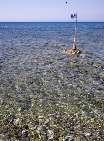 Aegean sea, seagull, boats seen at a beach in Greece Stock Photo