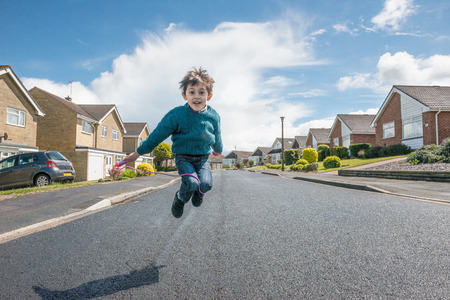 persona saltando: Un niño feliz en una carretera del desierto saltando con una cuerda