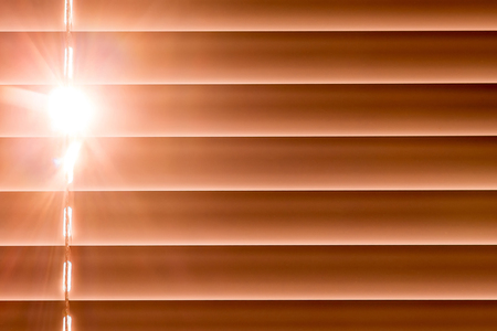 orange horizontal blinds on the window create a rhythm, through the intervals the light passes through