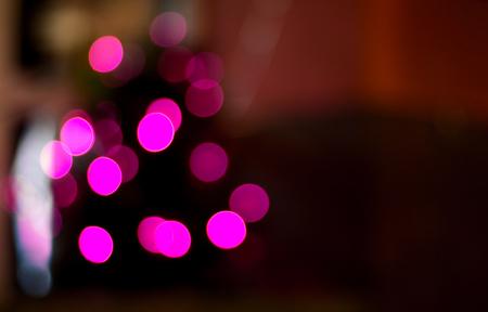 밝은 핑크 퍼지 bokeh 광선과 어두운 배경에 빛난다.