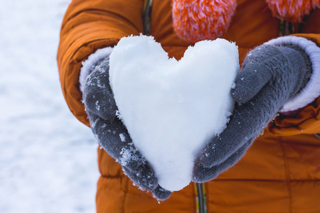 girl holding a heart of snow, wishes to congratulate her friend on Valentines Day and wish her happiness and love