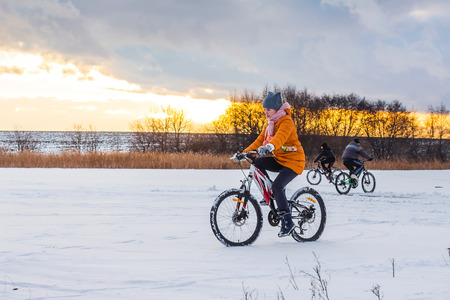 girl on a bicycle in winter rides on ice against a background of a pre-recess sky Stock Photo