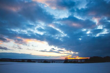 日没時の空は、明るく、はっきりと表現された嵐の雲で覆われ、下は海岸と川です 写真素材