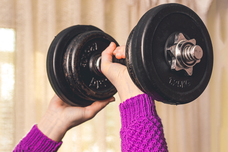 a young girl does sports, she lifted a heavy dumbbell Banco de Imagens